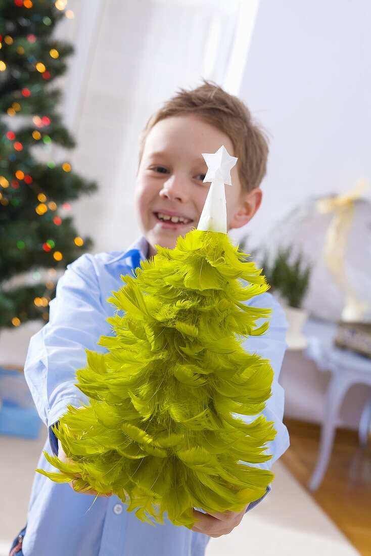 Little boy holding a feather Christmas tree