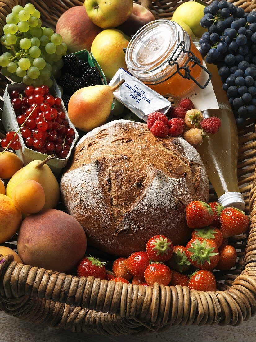 Fruit, bread, butter and honey in basket