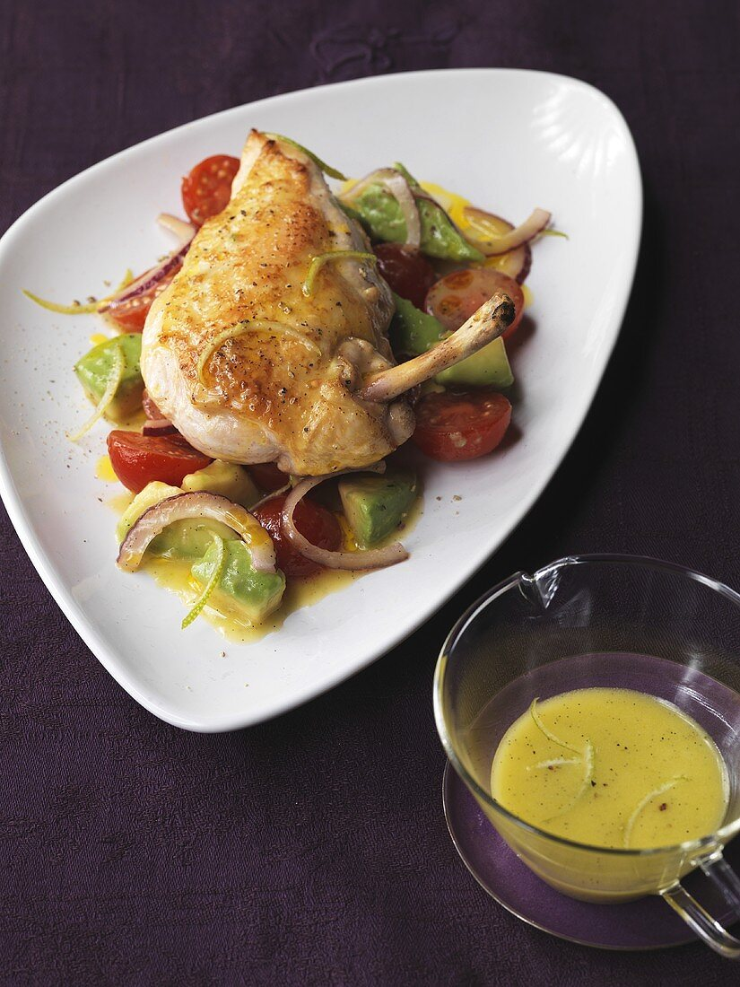 Roast chicken breast on avocado and tomato salad