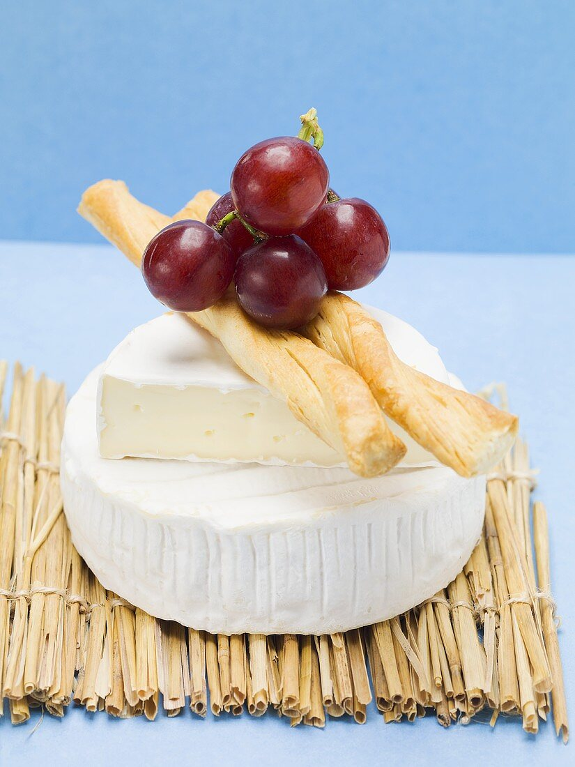 Camembert, savoury sticks and grapes on straw mat