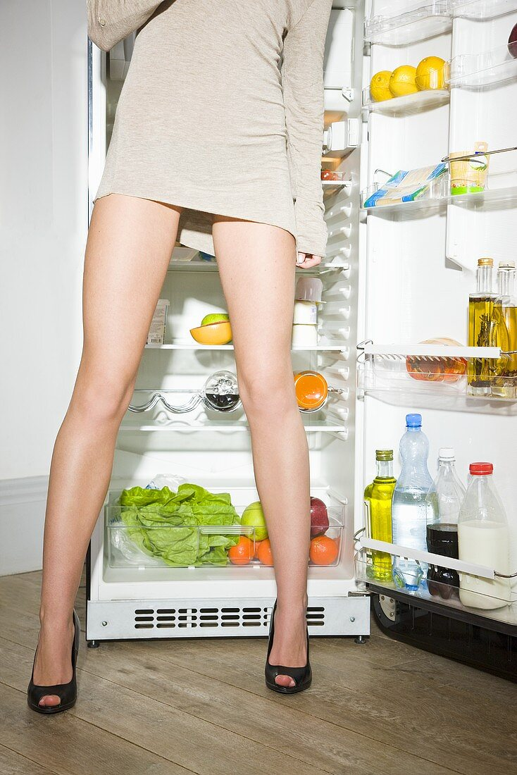 Young woman standing in front of opened refrigerator