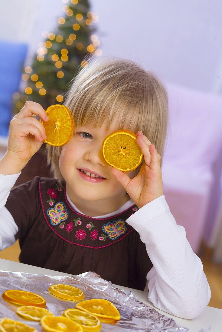 Little girl with dried orange slices