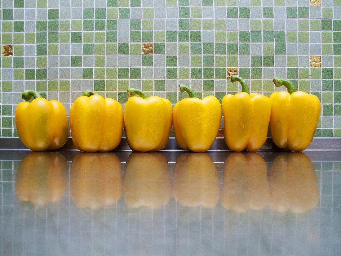 Six yellow peppers on stainless steel worktop