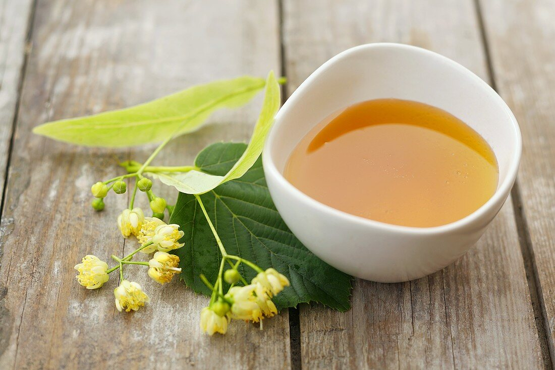 Lime blossom honey in a small dish with lime blossom