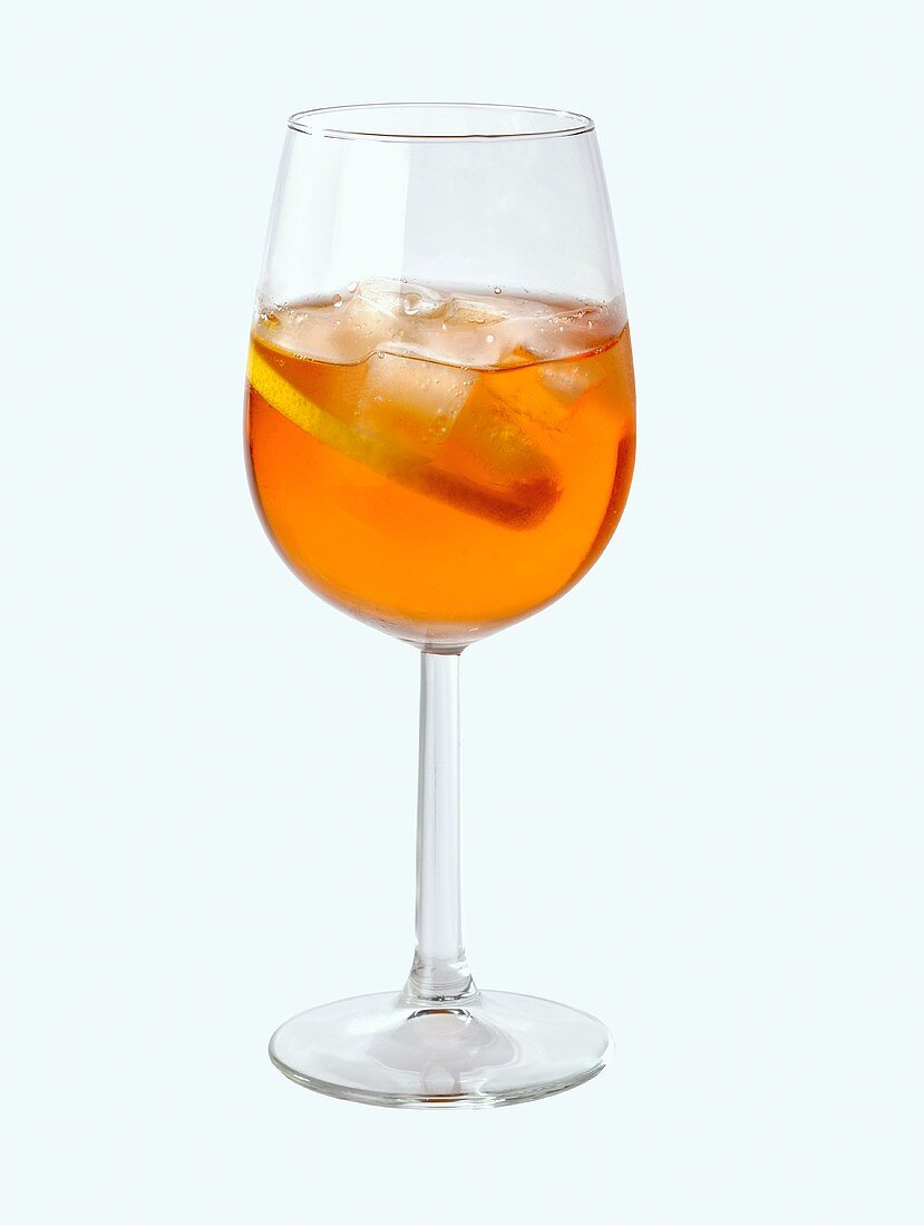 A glass of Aperol with ice cubes and slice of lemon