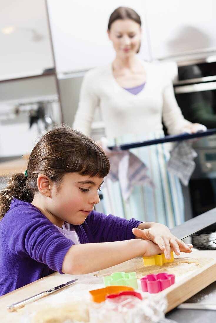 Mother and daughter baking biscuits
