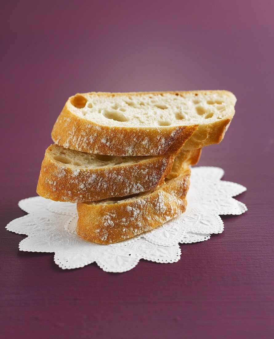 Three slices of baguette on white doilies