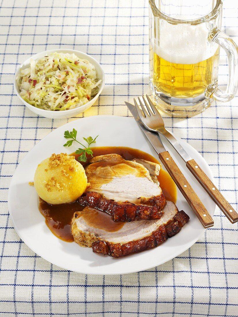 Roast pork with potato dumpling, cabbage salad and beer