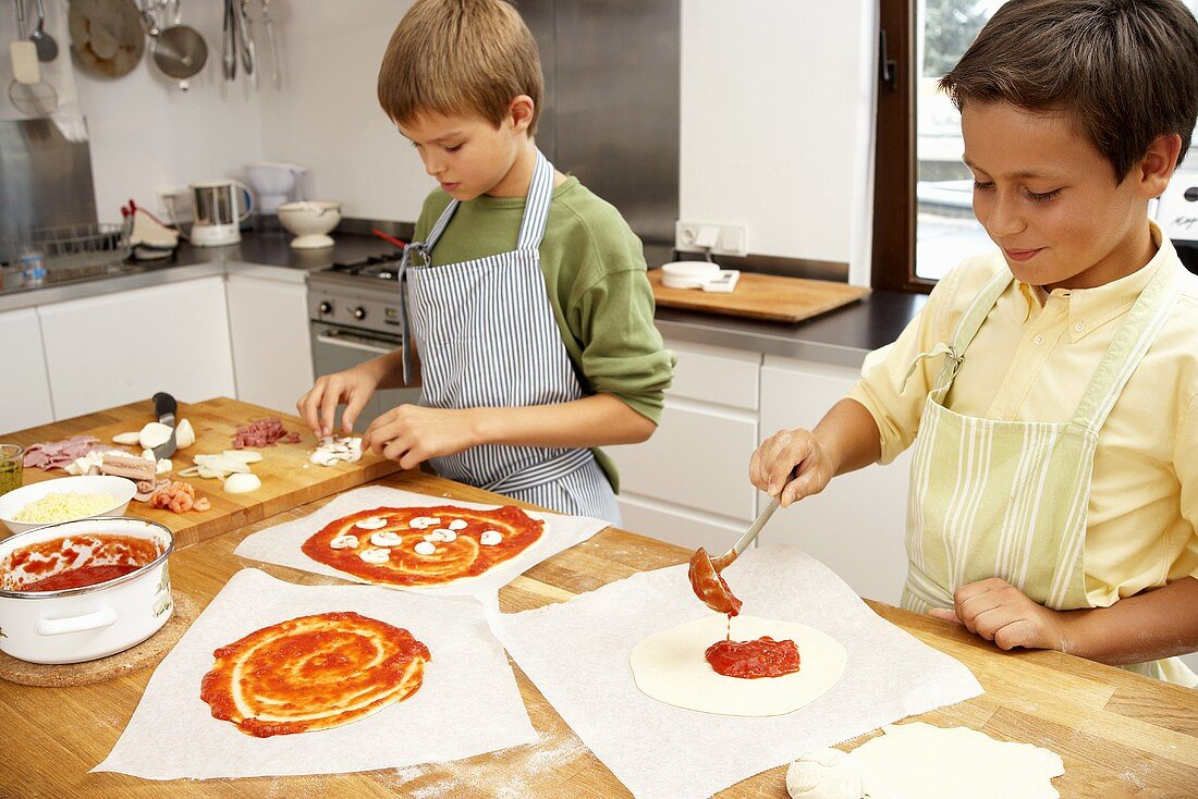 Two boys putting toppings on pizzas