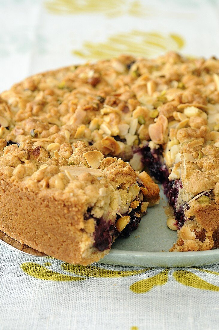 Crumble cake with flaked almonds, a piece cut