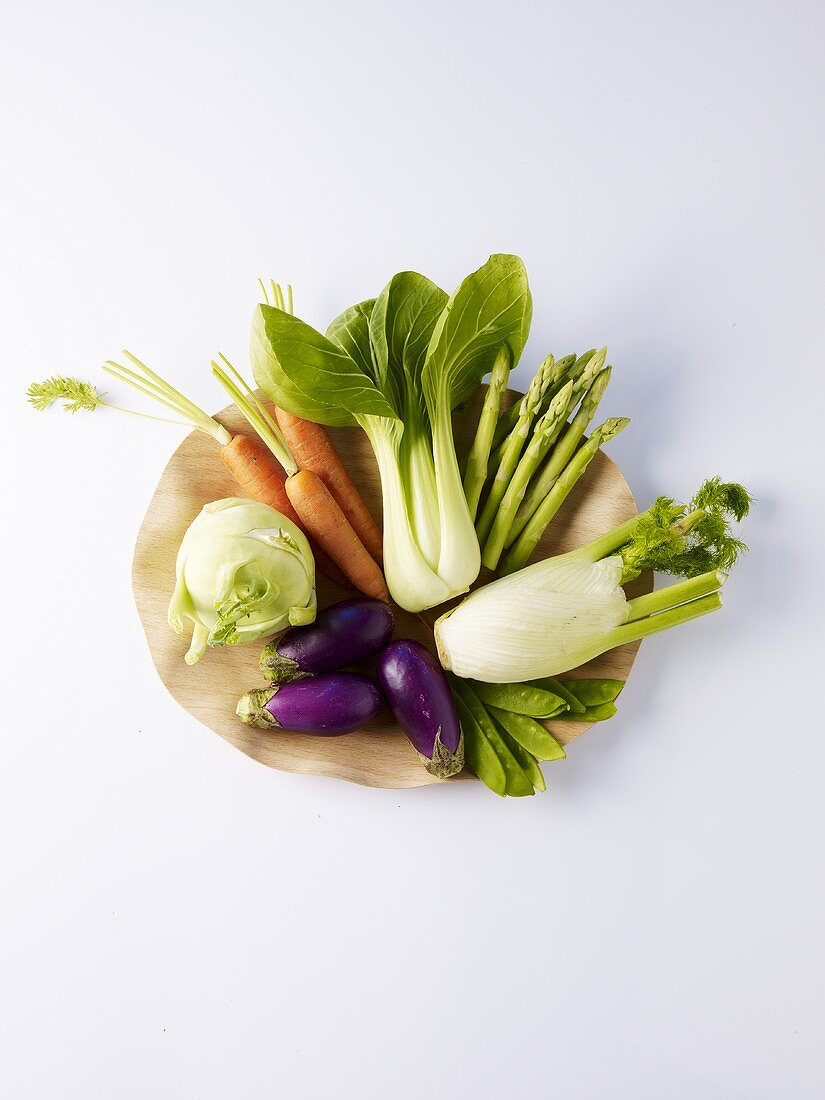 Assorted vegetables on a wooden plate
