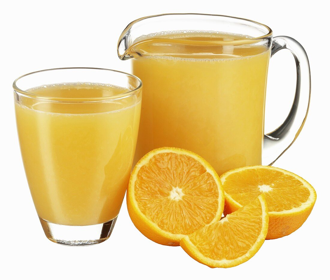 Orange juice in jug and glass with fresh oranges