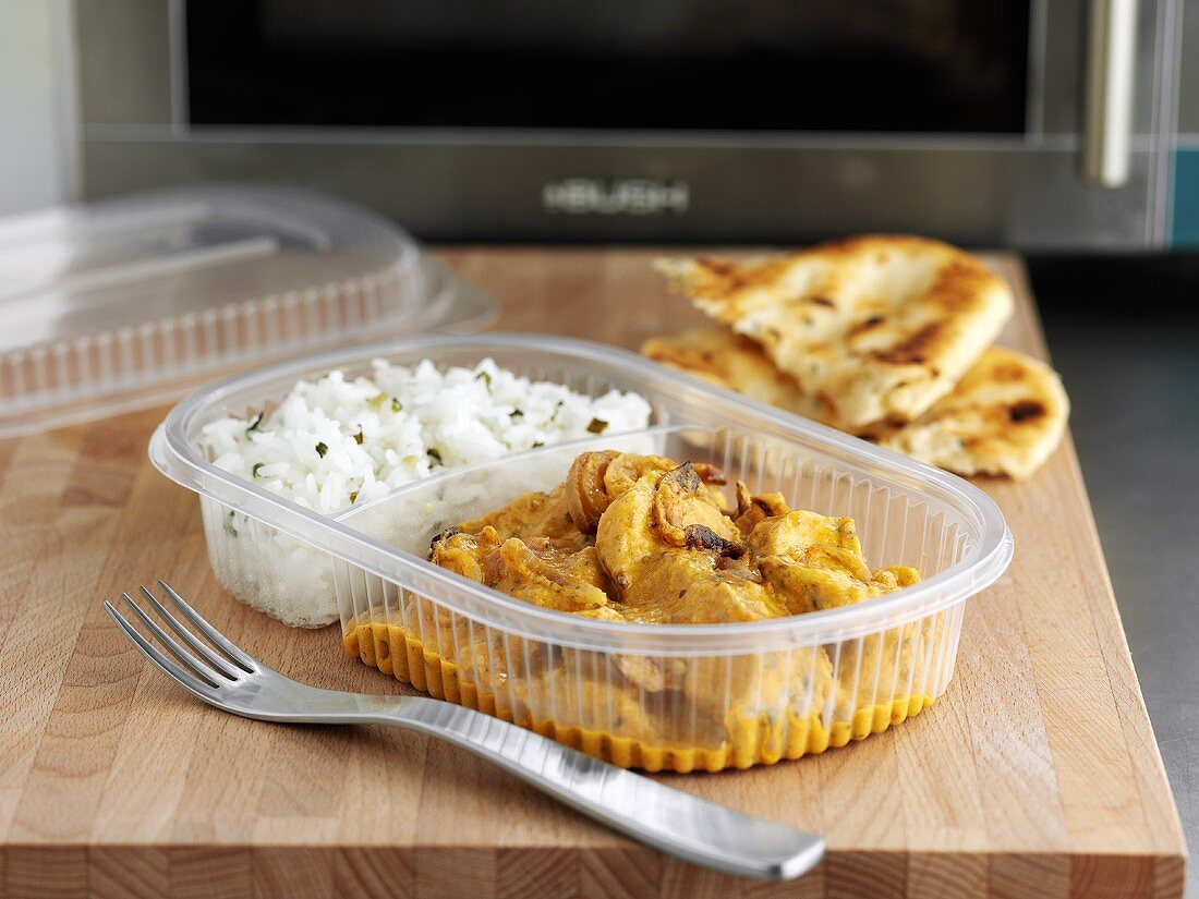 Indian ready-meal in plastic container in front of microwave oven