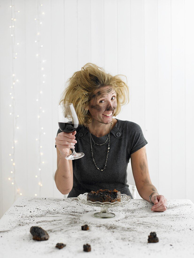 Woman with red wine sitting in front of exploded Christmas pudding
