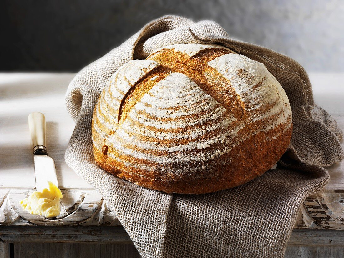 Round rustic bread on a jute bag, butter