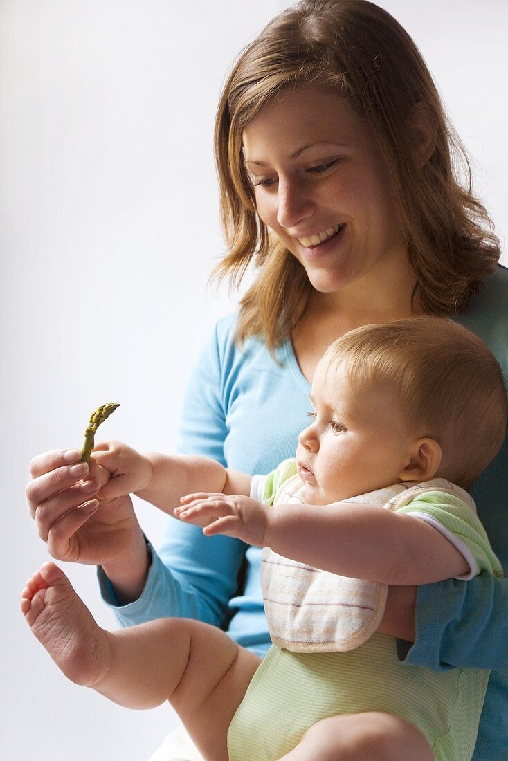 Mother giving baby asparagus tip