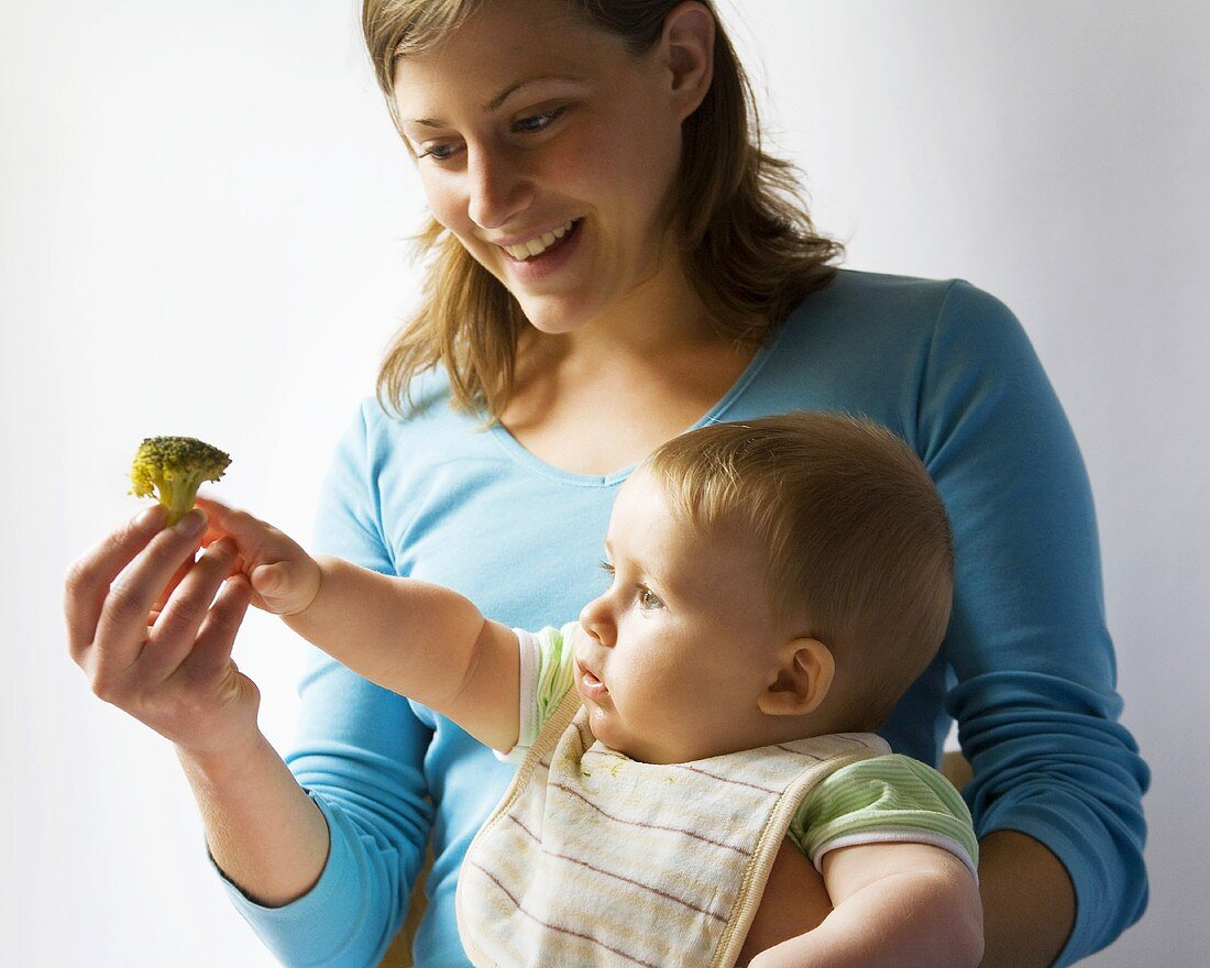 Mother giving baby a broccoli floret