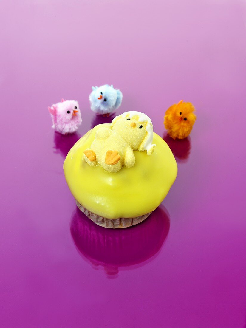 Muffin with yellow icing and jelly chick for Easter