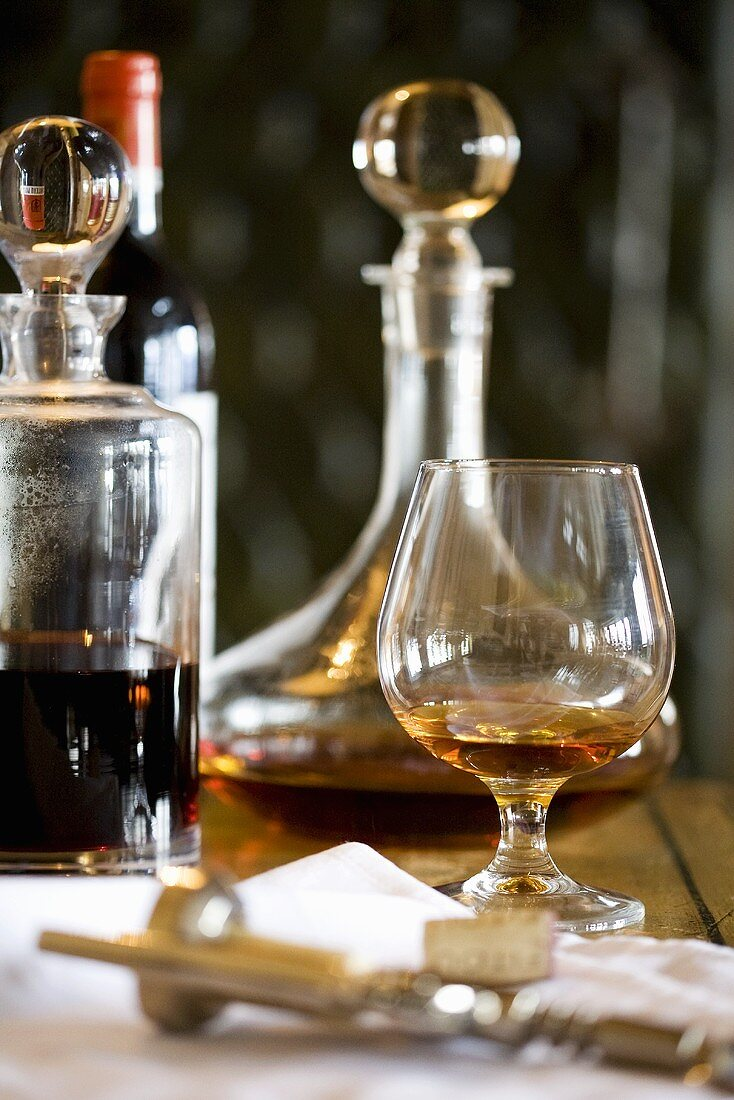 Glass of brandy, decanters, bottle of wine and corkscrew