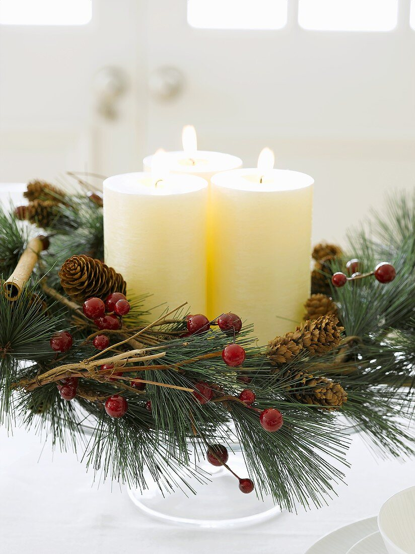Candles and Christmas wreath on cake stand