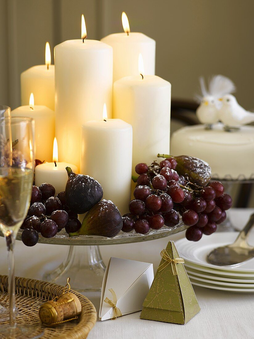 Christmas table decoration with candles, grapes and figs
