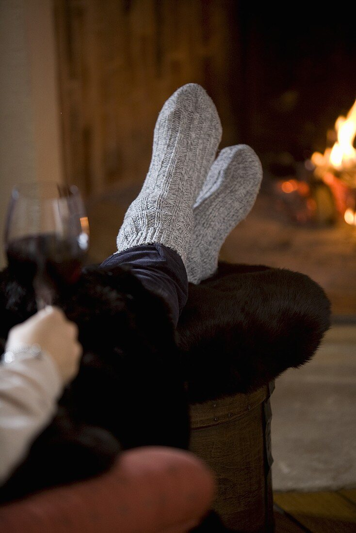 Woman with glass of red wine in front of fire