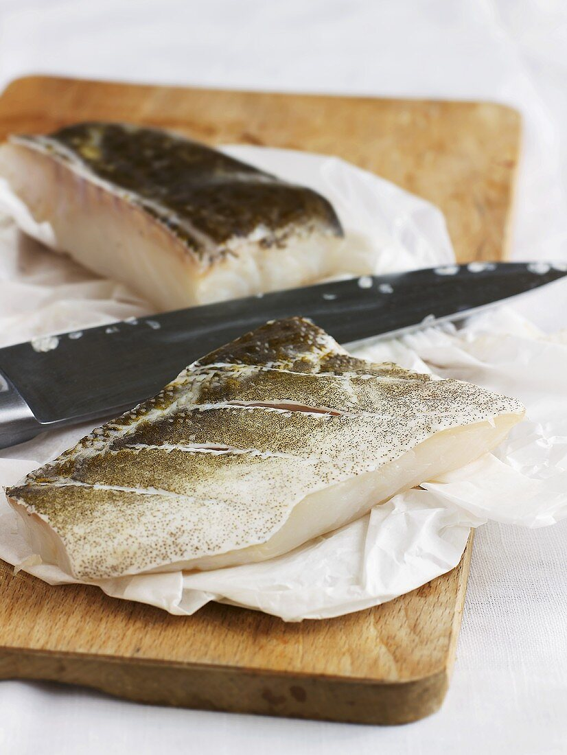 Pieces of cod fillet on paper on chopping board
