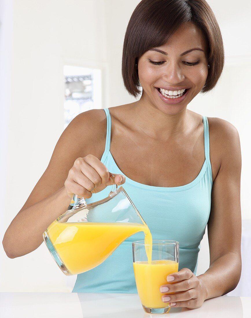 A woman pouring orange juice into a glass