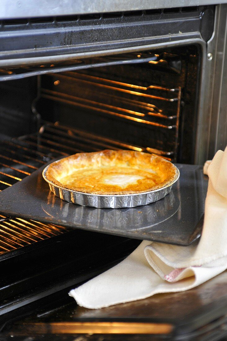 A pre-baked Bakewell tart being removed from the oven