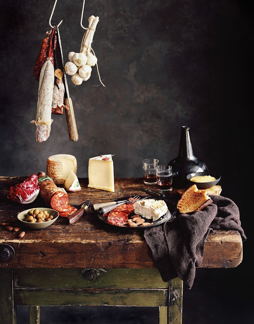 An arrangement of meats, cheese, olives, bread and wine