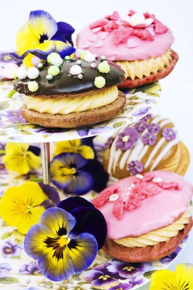 Various whoopie pies on a cake stand with pansies