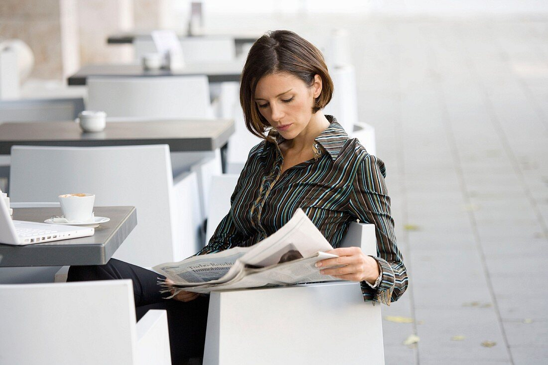 Woman sitting in a cafe reading a newspaper