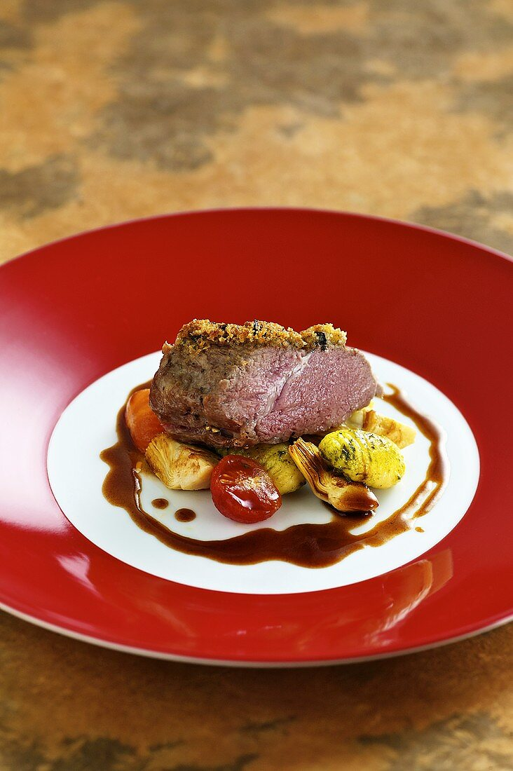 Saddle of lamb with an olive crust with artichoke and gnocchi