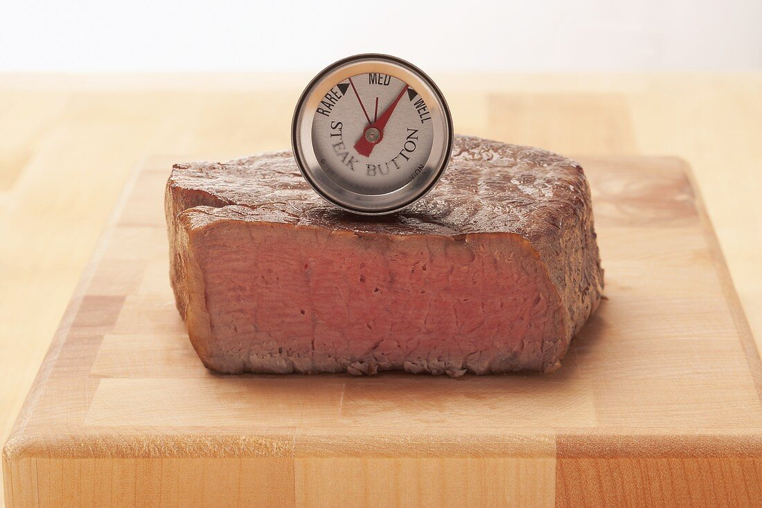 The core temperature of a beef steak being taken (well done)