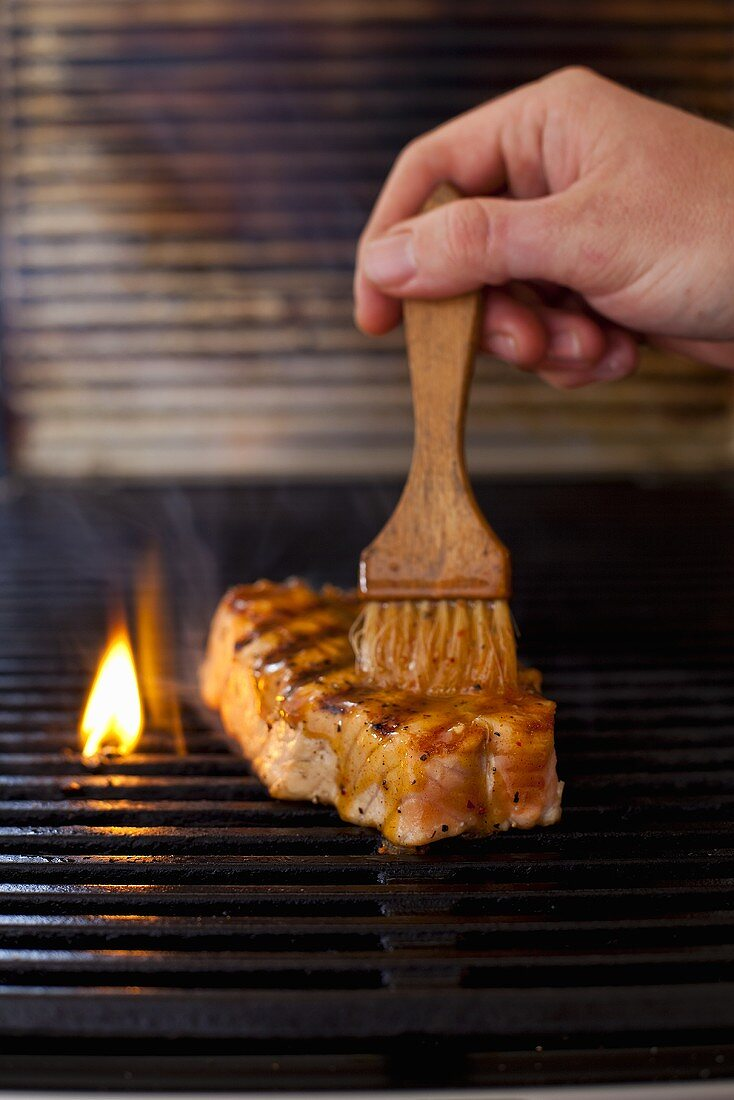 Tuna steak being brushed with a barbeque marinade