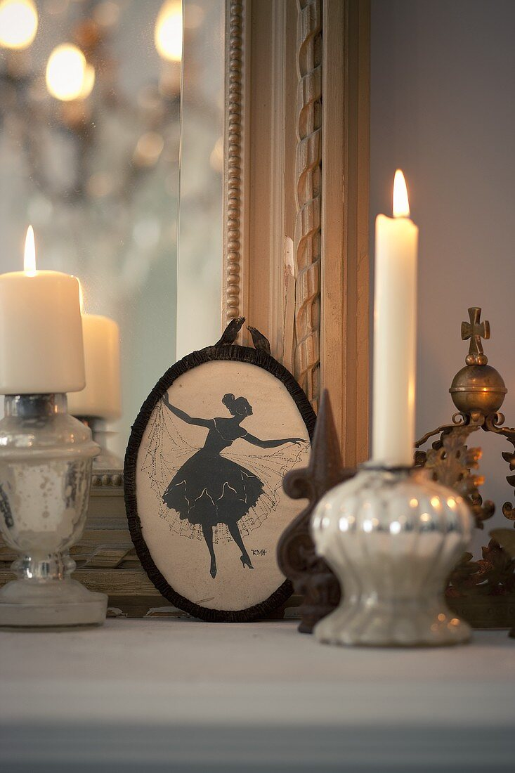 Silver candle sticks and a picture on the mantelpiece