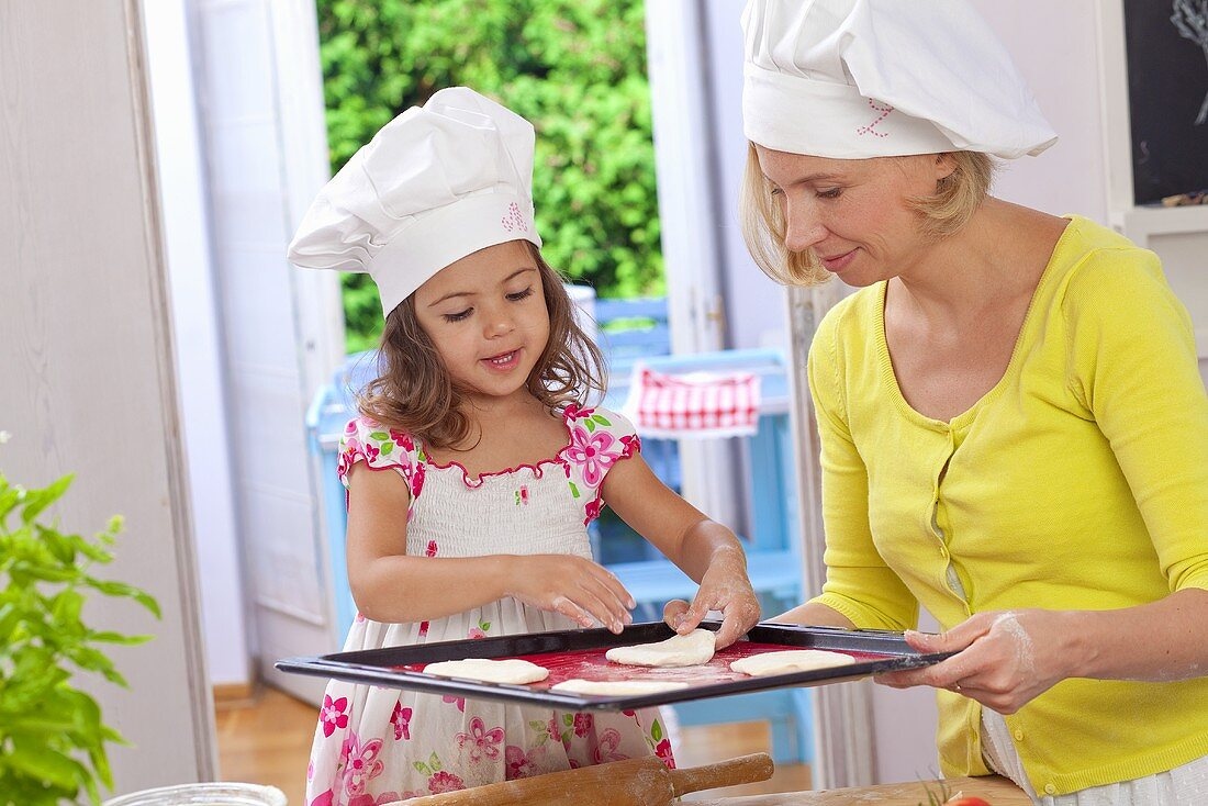 A mother and daughter placing pizza dough on a baking tray