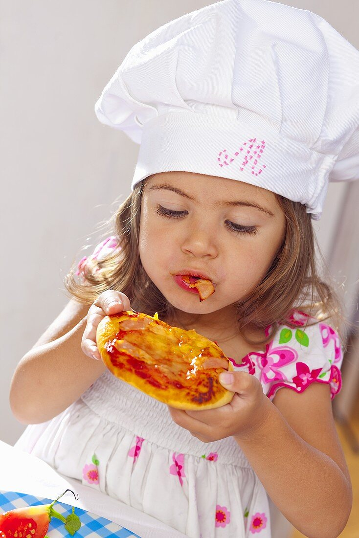 A little girl eating a mini pizza
