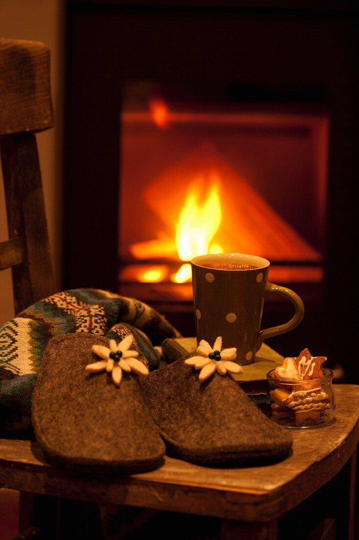 Felt slippers, gingerbread and cocoa on a stool in front of a fire