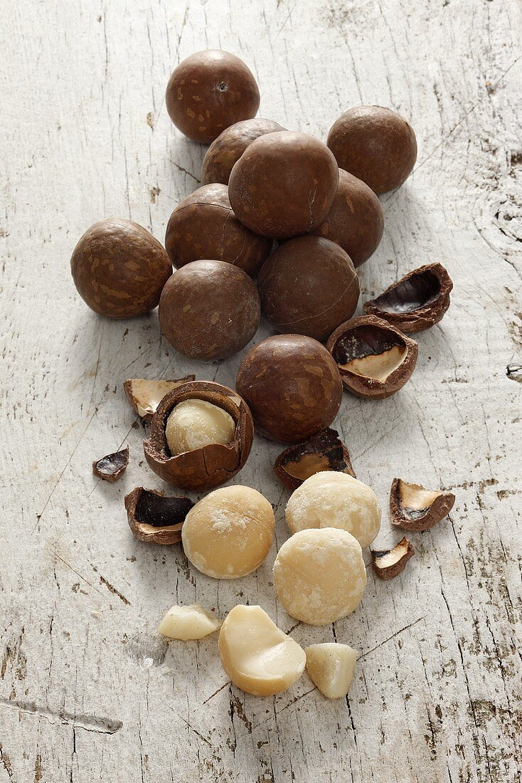 Macadamia nuts, with and without shells on a white wooden surface
