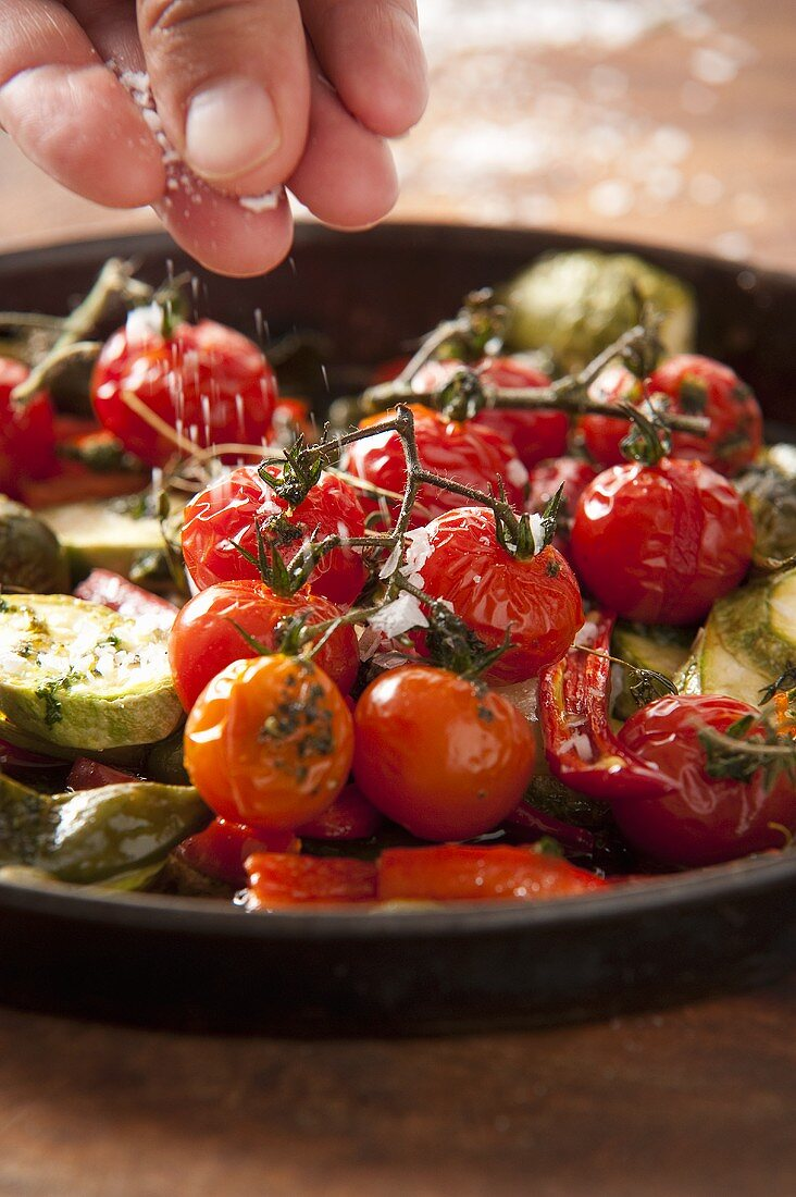 Roasted cherry tomatoes being sprinkled with fleur de sel