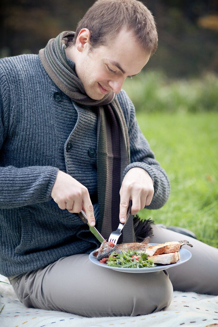 A man sitting on a picnic blanket eating grilled fish