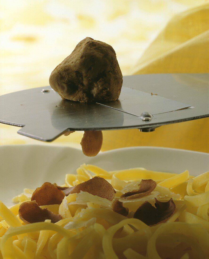 Shaving truffle over pasta
