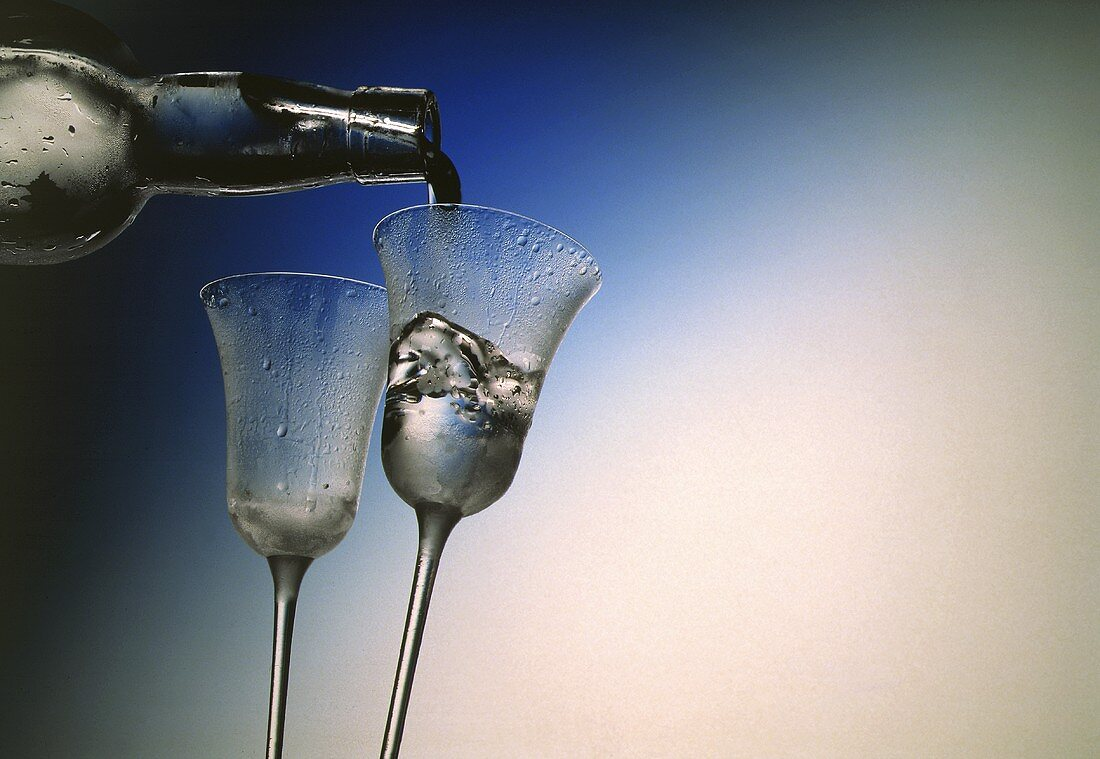 Pouring Schnapps into Two Chilled Stem Glasses