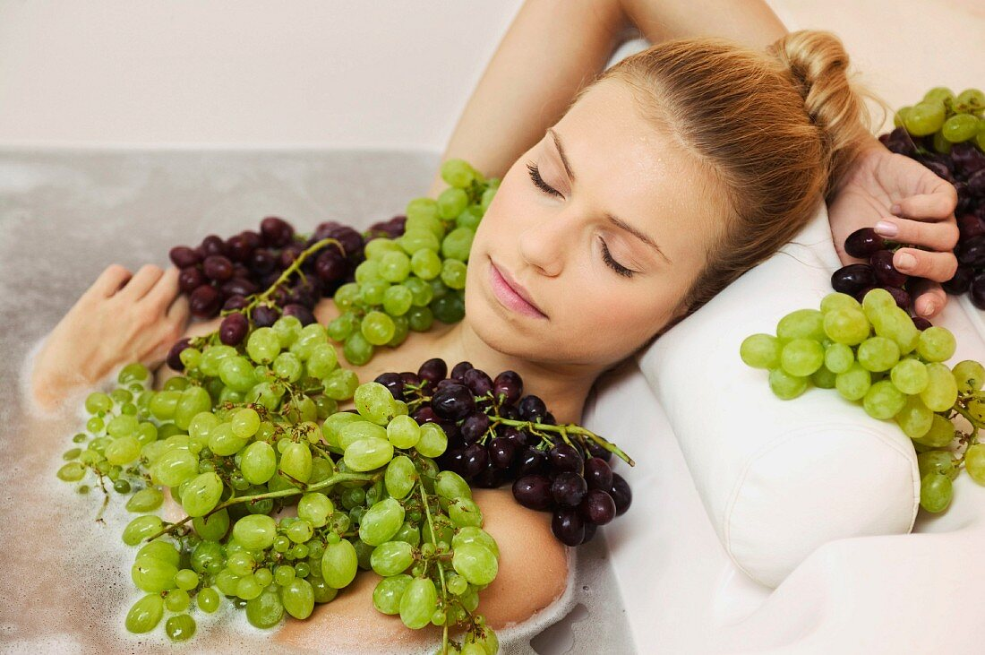 Young woman in bath with grapes