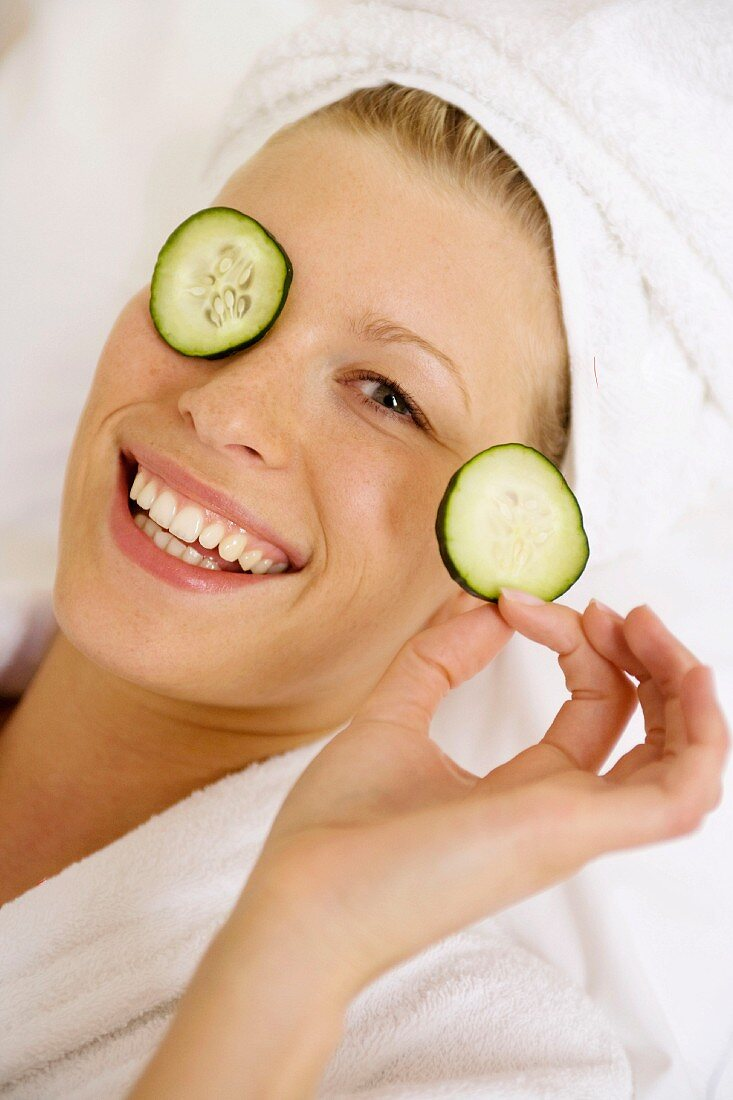 Young woman with slices of cucumber on her eyes