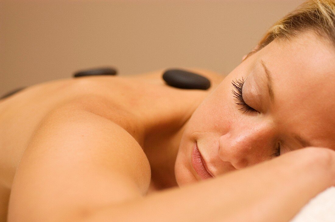Young woman relaxing during stone massage