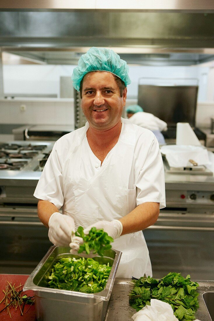 A worker in a commercial kitchen prepared salad