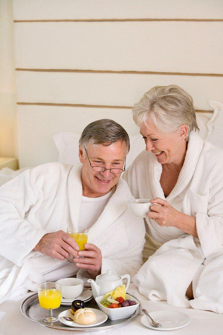 Older married couple eating breakfast in bed