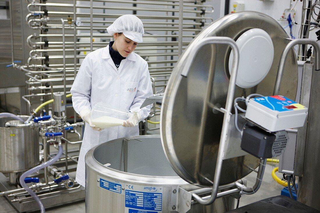 Food technician pasteurising milk